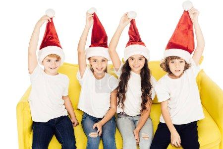 Photo pour Sourire adorables enfants tenant des chapeaux de santa et assis sur le canapé jaune isolé sur blanc - image libre de droit
