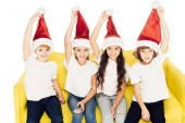 smiling adorable kids holding santa hats and sitting on yellow sofa isolated on white