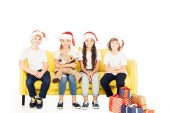 adorable kids in santa hats sitting on yellow sofa with teddy bear and presents isolated on white