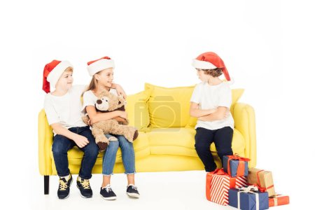 Photo for Adorable kids in santa hats hugging on yellow sofa, angry boy sitting with crossed arms isolated on white - Royalty Free Image