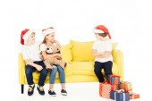adorable kids in santa hats hugging on yellow sofa, angry boy sitting with crossed arms isolated on white