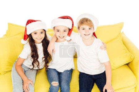 Foto de Alto ángulo de visión de niños adorables sonrientes con sombreros de santa sentado en el sofá amarillo y mirando a cámara aislada en blanco - Imagen libre de derechos