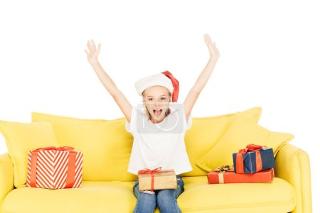 happy adorable child in santa hat screaming with raised hands isolated on white, looking at camera