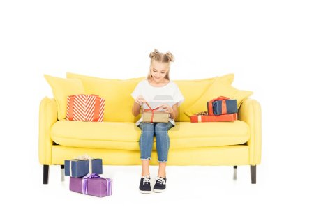 Photo for Smiling adorable child opening present on yellow sofa isolated on white - Royalty Free Image