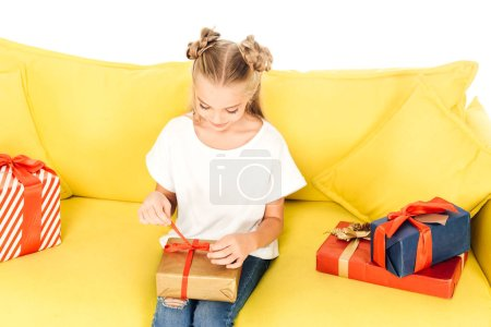 high angle view of adorable child opening present on yellow sofa isolated on white