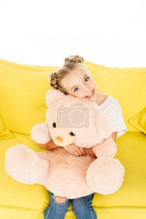 smiling adorable child hugging teddy bear on yellow sofa isolated on white, looking at camera