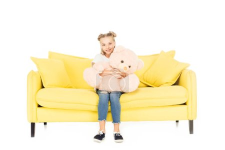 smiling adorable child sitting with teddy bear on yellow sofa isolated on white