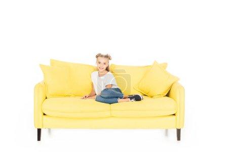 Foto de Adorable niño sentado en el sofá amarillo y mirando a cámara aislada en blanco - Imagen libre de derechos