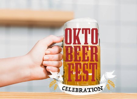 """partial view of female bartender putting mug of light beer with foam on bar counter with """"oktoberfest celebration"""" lettering"""