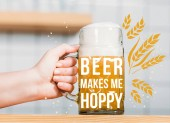 """partial view of female bartender putting mug of light beer with foam on bar counter  with """"beer makes me hoppy"""" inspiration"""