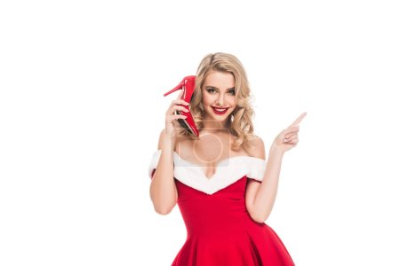 smiling young woman in christmas dress talking on shoes with heels and pointing by finger isolated on white