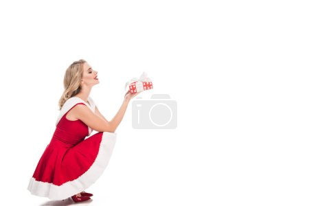 side view of sexy santa girl sitting with gift box isolated on white