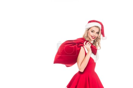happy young woman in santa dress holding christmas sack over shoulder isolated on white