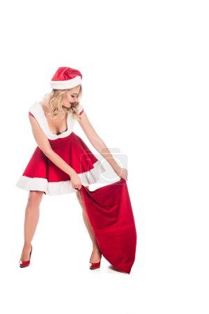 smiling santa girl in dress pulling christmas sack isolated on white