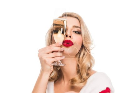 portrait of young woman in christmas dress covering face by champagne glass isolated on white