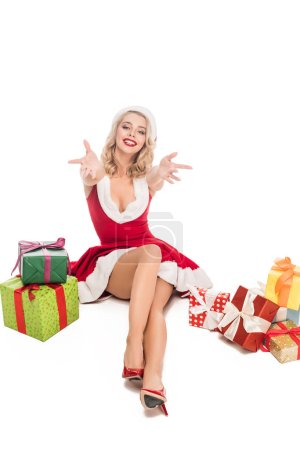 beautiful young woman in christmas dress sitting with wide arms near pile of gift boxes isolated on white