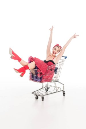 excited young woman in pin up dress sitting with raised arms in shopping trolley isolated on white