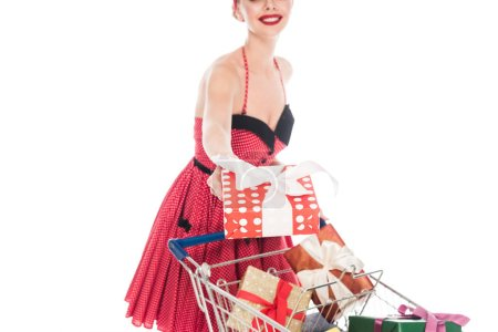 partial view of pin up woman carrying shopping cart with pile of gift boxes and giving present isolated on white