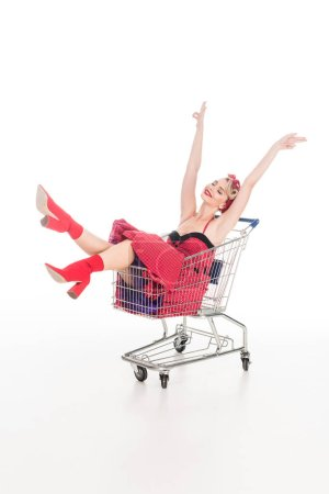 Photo for Young woman in pin up dress sitting with raised arms in shopping trolley isolated on white - Royalty Free Image