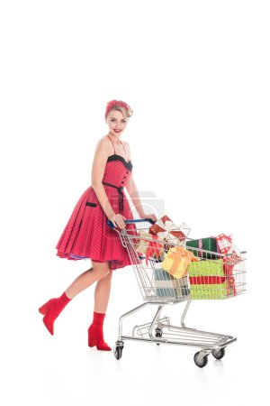attractive pin up woman carrying shopping cart with pile of gift boxes isolated on white