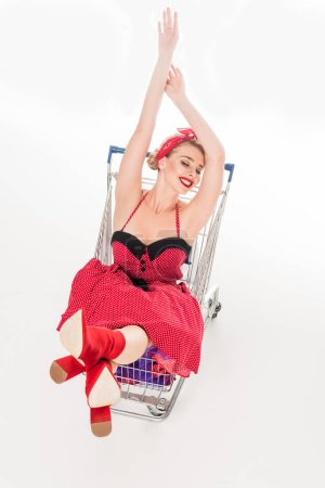 Photo for High angle view of attractive pin up woman sitting with raised arms in trolley isolated on white - Royalty Free Image