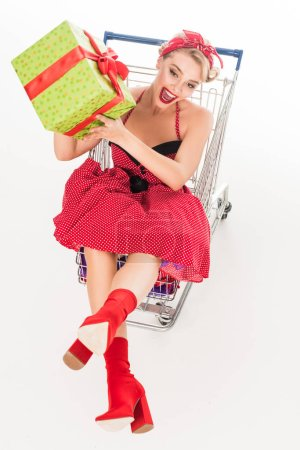 high angle view of happy woman in retro clothing with gift sitting in shopping cart isolated on white