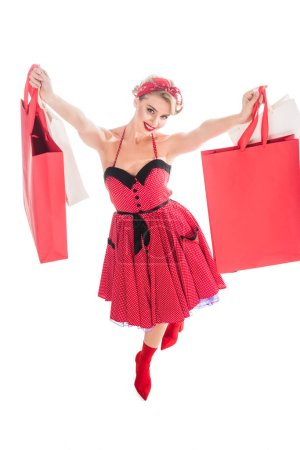 high angle view of smiling woman in retro dress with shopping bags isolated on white