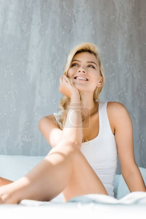 low angle view of happy young woman in underwear sitting on bed and looking away