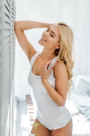 beautiful happy blonde girl in white underwear standing with closed eyes in bedroom