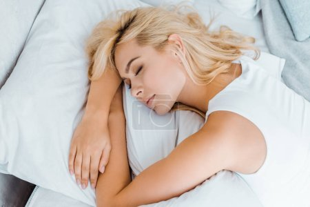 high angle view of beautiful young blonde woman sleeping on bed