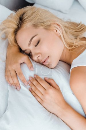 close-up view of beautiful young blonde woman sleeping on bed