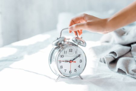 Photo for Close-up partial view of young woman holding alarm clock in bedroom - Royalty Free Image