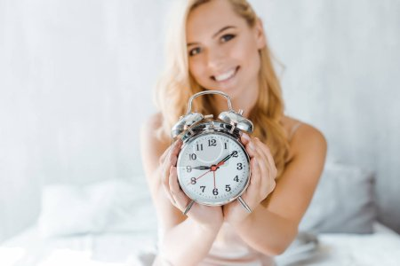 close-up view of beautiful young woman holding alarm clock and smiling at camera in bedroom