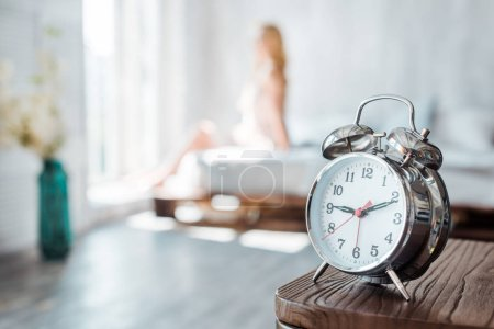 Photo for Close-up view of alarm clock on wooden table and young woman sitting on bed behind - Royalty Free Image