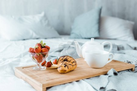 Photo for Close-up view of tasty breakfast on wooden tray on bed - Royalty Free Image