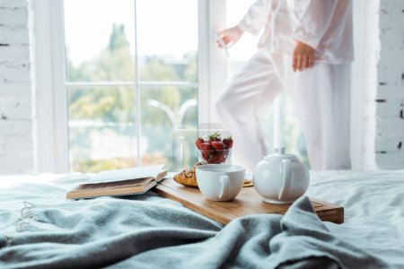 cropped image of woman opening window, breakfast and book on bed