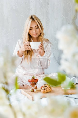 Photo for Beautiful woman in pajamas drinking tea in bed in morning - Royalty Free Image