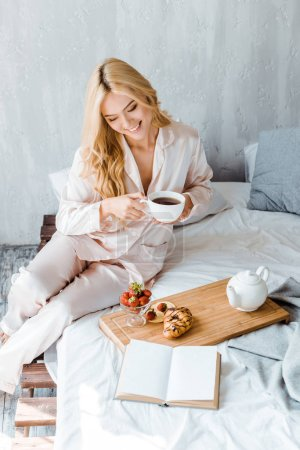 high angle view of beautiful smiling woman holding cup of tea in bed in morning