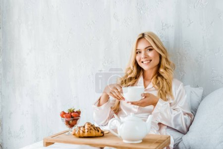 Photo for Beautiful smiling woman holding cup of tea in bed in morning and looking at camera - Royalty Free Image
