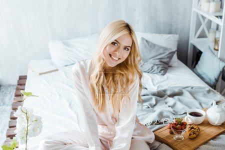 smiling attractive woman in pajamas looking at camera, breakfast on wooden tray in bed