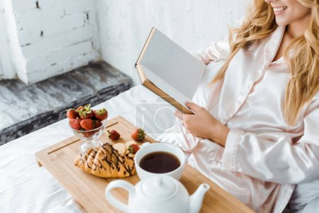 Photo for Cropped image of attractive woman in pajamas reading book, breakfast on wooden tray in bed - Royalty Free Image