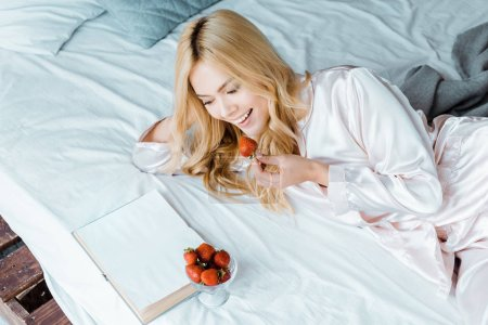 laughing attractive woman in pajamas eating strawberry and reading book in bed in morning