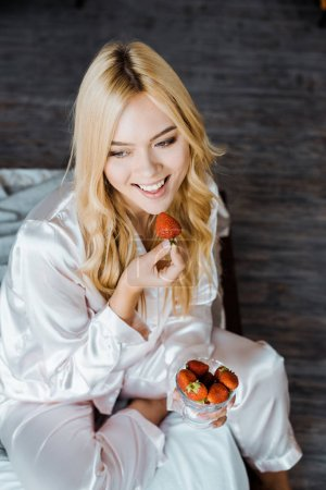 high angle view of attractive woman in pajamas eating strawberry in bed in morning