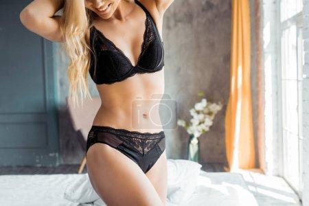 Photo pour Image recadrée de femme attrayante en lingerie noire debout dans la chambre - image libre de droit