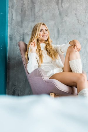 Photo for Attractive woman in sweater sitting in chair in morning and looking away - Royalty Free Image