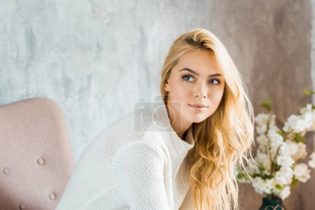 portrait of beautiful woman in sweater sitting on armchair in bedroom and looking away