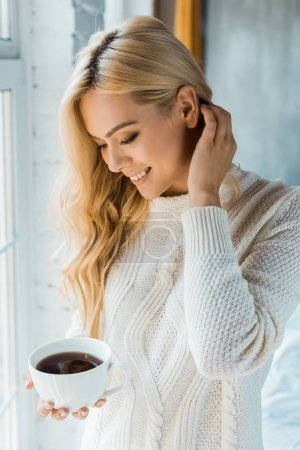 Photo pour Souriant attrayant femme en pull tenant tasse de café dans la chambre le matin - image libre de droit