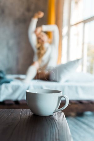 selective focus of attractive woman in sweater stretching in bedroom in morning, cup of coffee on tabletop