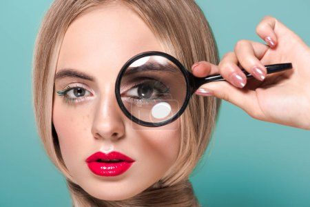 beautiful young woman holding magnifying glass and looking at camera isolated on blue