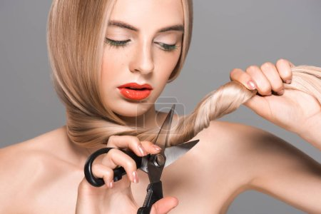 beautiful naked girl cutting long hair with scissors isolated on grey